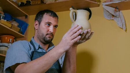 Professional male potter examining ceramic jug with handle in workshop, studio. Handmade, small business, crafting work concept Banco de Imagens