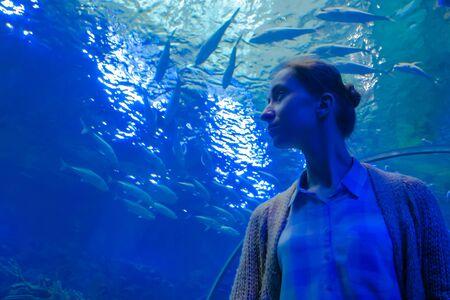 Portrait of woman looking at fish vortex in large public aquarium tank with blue illumination at oceanarium. Tourism, education, underwater life and entertainment concept
