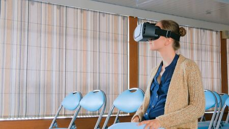 Young woman using virtual reality headset in the empty conference hall. Technology and entertainment concept