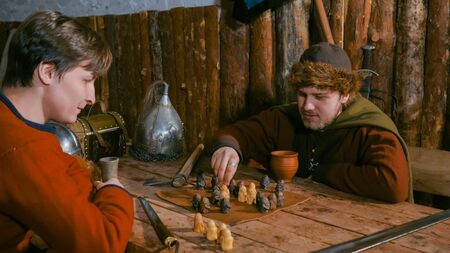 Two men in russian ethnic suit playing medieval popular strategy board game - tafl. Folk, competition and traditional concept