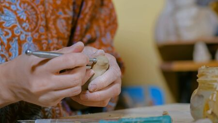 Professional woman potter making ceramic souvenir penny whistle toy bird in pottery workshop, studio. Crafting, artwork and handmade concept Banco de Imagens