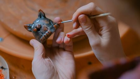 Professional woman potter, decorator painting ceramic souvenir penny whistle toy cat in pottery workshop, studio. Crafting, artwork and handmade concept