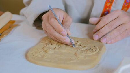 Professional male potter making clay stamp picture. Handwork, crafting and traditional arts concept Banco de Imagens