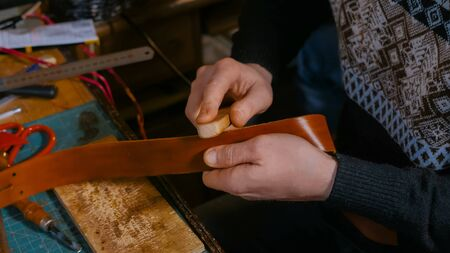 Professional male skinner, tanner working with genuine leather belt at workshop, studio. Handmade and leatherwork concept Banco de Imagens