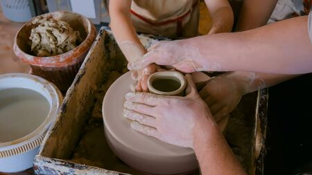 Pottery class and workshop: professional male potter working with children and showing how to make ceramic wares in pottery studio. Handmade, education and study concept Stock Photo