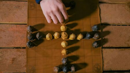 Game preparation - close up shot of man hand placing figures for medieval popular strategy board game - tafl. Folk, competition and traditional concept