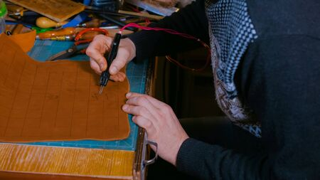 Professional male skinner, tanner making decorative details on leather playing field for strategy board game -tafl with special pyrographic machine