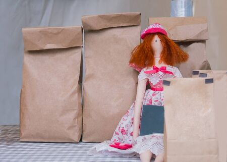Handmade red hair doll and blank brown kraft paper packets with tea at outdoor market