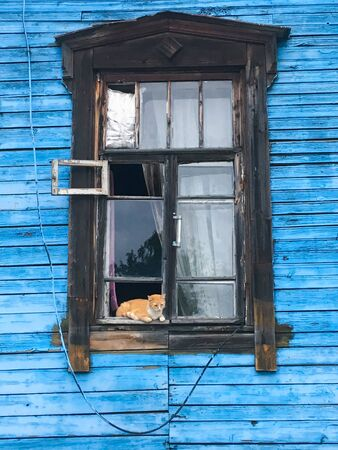 Red cat looks at the street from the window of old wooden house