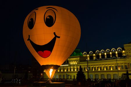 Hot air balloon with yellow smiley face at night festival