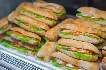 Assortment of sandwiches with lettuce, salmon, ham for sale on counter of market, cafe, store, shop or bakery. Take away, healthy, street, fast food concept Reklamní fotografie