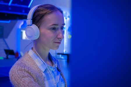Woman looking at exposition, using white headphones and listening audio guide at modern futuristic exhibition or museum. Education, sci-fi, interactive, technology, future and entertainment concept
