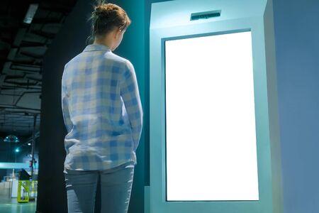 Écran blanc, maquette, futur, espace de copie, modèle, isolé, concept technologique. Femme regardant un écran tactile blanc interactif vierge d'un kiosque électronique à une exposition ou à un musée futuriste Banque d'images
