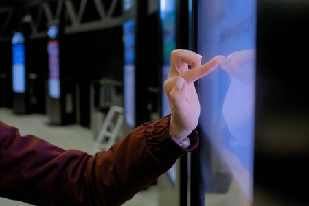Woman hand using interactive touchscreen display of electronic multimedia kiosk at modern museum or exhibition - scrolling and touching - close up view. Education, futuristic and technology concept Banco de Imagens