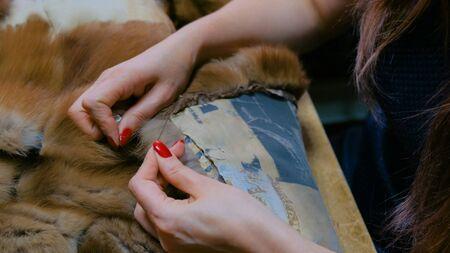 Professional tailor, designer repairing fur coat at atelier, studio. Fashion and tailoring concept Standard-Bild
