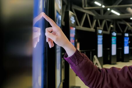 Education, entertainment, learning, technology concept - close up view of woman hand using interactive touchscreen display of electronic kiosk at public transport station - scrolling and touching