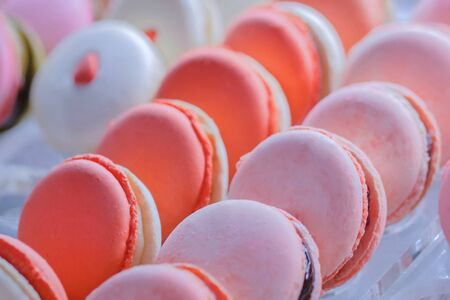 Close up view of colorful macarons for sale in showcase of candy shop, cafe or bakery. Traditional french cuisine, candy and sweet food concept Banco de Imagens
