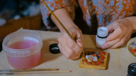 Professional woman potter, decorator painting ceramic souvenir refrigerator magnet in pottery workshop, studio. Crafting, artwork and handmade concept
