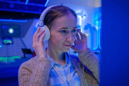 Femme regardant l'exposition, utilisant des écouteurs blancs et écoutant un audioguide dans une exposition ou un musée futuriste moderne. Concept d'éducation, de science-fiction, d'interactivité, de technologie, d'avenir et de divertissement