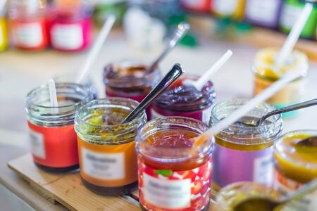 Delicious colorful jam, jelly or confiture in little glass jar for tasting on counter of shop, market, cafe. Dessert, sweet food and confectionery concept