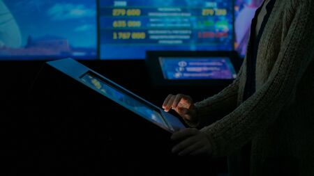 Woman using interactive touchscreen display in modern historical museum. Evening time, lowlight. Education and entertainment concept. Close up shot
