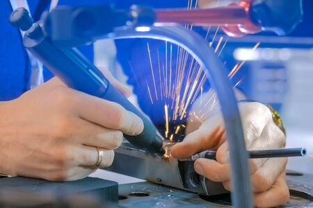 Professional male welder trying gas tungsten arc welding GTAW or tungsten inert gas TIG technology at exhibition or trade show - close up view of man hands. Industrial concept and engineering work
