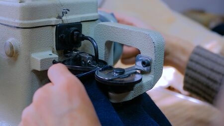 Professional male skinner, furrier using special sewing machine for stitching beaver fur skin at atelier, workshop. Fashion and leatherwork concept