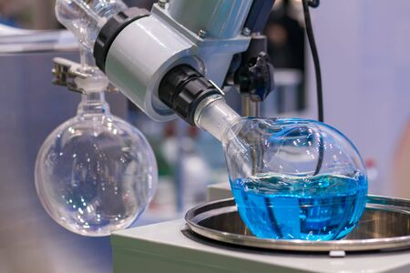 Laboratory rotary evaporator - homogenization process - rotating chemical flask for evaporate solvent from blue liquid at pharmacy factory or medical exhibition. Pharma, chemistry and science concept Foto de archivo