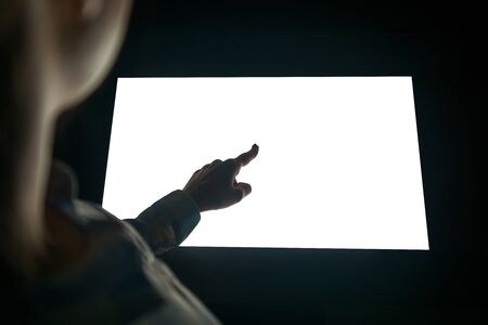 Mockup image - woman touching white empty interactive touchscreen display kiosk in dark room