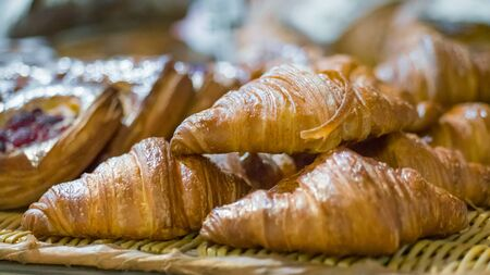 Assortment of freshly baked croissants for sale on counter of shop, market, cafe or bakery. Dessert, pastry, breakfast, sweet food and traditional french cuisine concept Stockfoto