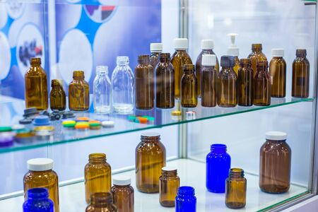 Medical empty glass bottles in showcase at pharmaceutical exhibition, pharmacy laboratory. Pharma industry, science, medicine, experiment and healthcare concept