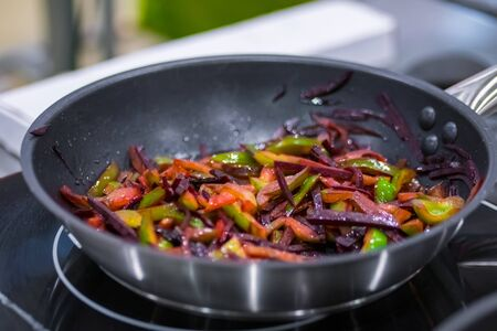 Process of cooking sliced pepper and beetroot in black frying pan with oil on electric stove at cuisine of restaurant. Professional cooking, catering, culinary, gastronomy and food concept Stockfoto
