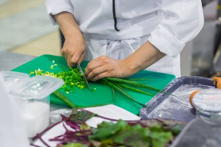 Chef hands chopping, cutting green onion, scalliion with knife at cuisine of restaurant. Professional cooking, catering, cookery, gastronomy and food concept Stockfoto
