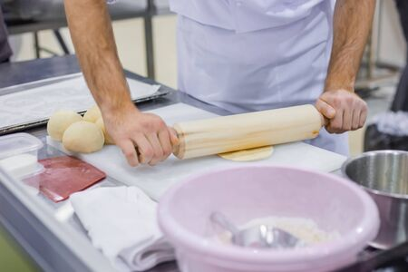 Professional cooking, catering, culinary, gastronomy and food concept. Baker, chef hands preparing fresh dough with rolling pin on kitchen table at cuisine of restaurant, bakery