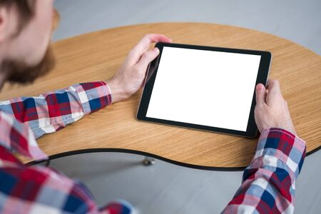 Man sitting at wooden table and looking at black digital tablet computer device with white blank screen. Mock up, entertainment, copyspace, template, leisure time and technology concept Stockfoto