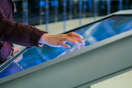 Education, futuristic and technology concept - woman using interactive touchscreen display of electronic kiosk at technology exhibition or modern museum - side close up view Stockfoto