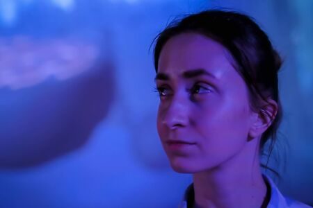 Portrait of woman face looking around at modern immersive exhibition with low light illumination and colorful video art installation. Education, digital art and entertainment concept