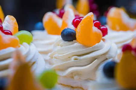 Close up view - assortment of delicious fresh shortcrust tart cakes with cream, fruits and berries for sale on counter of shop, market, cafe or bakery. Dessert, sweet food and confectionery concept