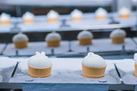 Ice-cream dairy factory - conveyor belt with icecream cones at modern food processing factory. Manufacturing, dairy industry, engineering and automated technology equipment concept