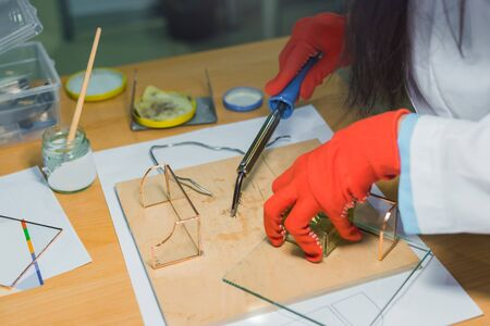 Professional woman decorator, designer working with soldering iron and making glass gift keepsake box at workshop, studio, close up view of female hands in orange gloves. Design, handmade, art concept