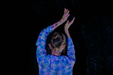 Woman waving her arms and dancing at modern immersive exhibition or club party with projector light illumination. Digital art, party and entertainment concept Stockfoto