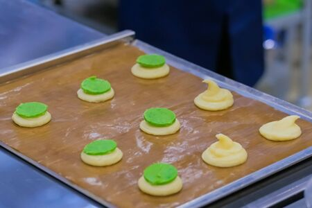 Process of preparing shortbread cookies with bright green filling on kitchen table at cuisine of bakery. Professional cooking, catering, bakery, gastronomy and food concept