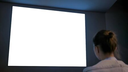 White screen, technology, isolated, futuristic, template, mock up, entertainment concept. Woman looking at large wall blank interactive white display at science exhibition, museum or cinema Stockfoto