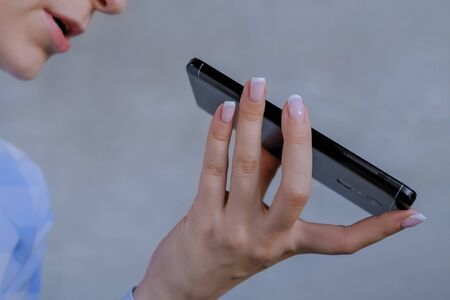 Authentication, communication, online technology concept. Woman holding smartphone device, using voice recognition function, recording audio message, talking with mobile assistant - close up side view