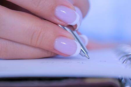 Woman hand with french manicure holding pen and writing to do list in vintage notebook organizer - close up top view. Motivation, management, productivity, success, planning, reminder, goals concept Stockfoto