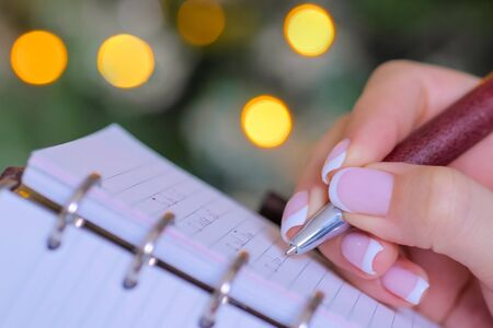 Christmas, motivation, management, productivity, planning, reminder, goals concept. Woman writing to do list in vintage notebook organizer - close up view. Garland light illumination bokeh background