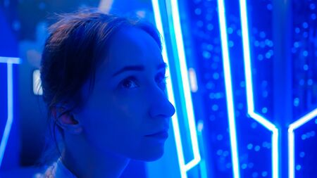 Portrait of young woman face looking around at modern futuristic exhibition or museum with sci-fi interior and blue illumination - close up view Education, technology and entertainment concept