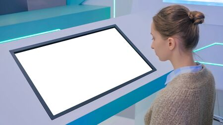 Woman looking at blank digital interactive white display kiosk at exhibition or museum with futuristic sci-fi interior. Mock up, copyspace, template, isolated, white screen, technology concept Stockfoto