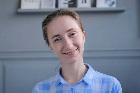 Portrait of young positive hipster, student or entrepreneur woman in blue plaid shirt smiling and looking at camera in room with grey wall. People and lifestyle concept