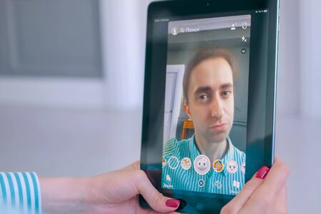 MOSCOW, RUSSIA - MAY 24, 2019: Woman using Snapchat multimedia messaging app with 3d face mask gender swap filter on tablet at home. Face detection technology, AR, selfie, gender switch concept